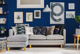 Different kind of pillows on comfortable grey corner sofa in elegant living room with blue wall with posters - 238382881