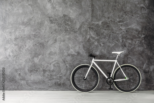 White bike on grey concrete wall, real photo with copy space