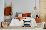 Copy space on white empty wall of trendy bedroom with flower in vase on wooden nightstand, king size bed with autumn colored bedding and wooden ladder