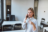Charming young woman talking on the phone and drinking coffee in modern office. - 238384240