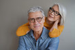 Portrait of relaxed fun senior couple wearing glasses on background