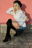 Portrait of stylish young woman in white shirt and knee high boots sitting on street - 238392489