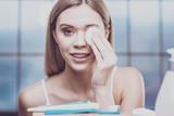 Young woman removing eye makeup