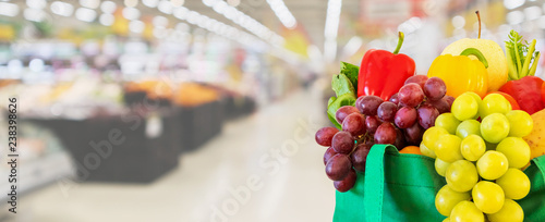 Fresh fruits and vegetables in reusable green shopping bag with supermarket grocery store blurred defocused background with bokeh light