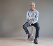 Full length casual senior man sitting on stool on gray background - 238404837