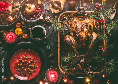 Leinwanddruck Bild Christmas dinner table with whole roasted turkey, stuffed with dried fruits served in roasting pan with sauce,red plates, cutlery, decoration and burning candles,  top view. Traditional Christmas food