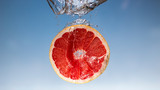 Fresh grapefruit with water splash on blue background close up