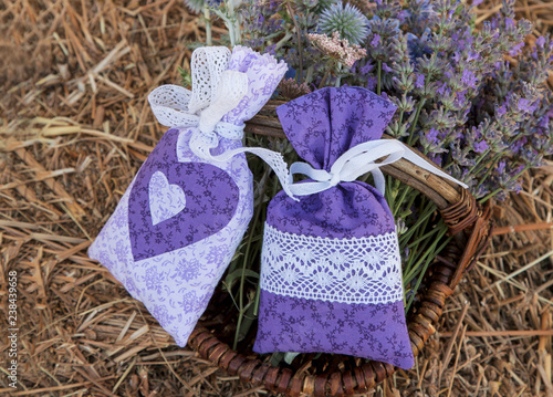 Pretty hand-sewn lace and fabric bags with lavender flowers In a wicker basket on straw
