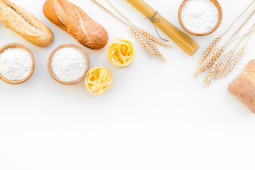 Farinaceous food. Fresh bread and raw pasta near flour in bowl and wheat ears on white background top view space for text