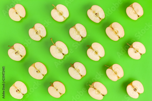 Fruit pattern on green background. Apple halves geometrical layout. Flat lay, top view. Food background. - 238472465