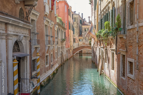 View of an empty romantic canal filled with sunlight. Venice, Italy.