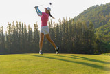 Asian woman golf player doing golf swing tee off on the green evening time, she presumably does exercise.  Healthy and Lifestyle Concept.