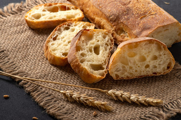 Italian traditional ciabatta bread with sliced pieces and ears of wheat lie on a jute napkin on a table.
