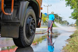 a worker spraying water to clean the road with pressurized water system, wet cleaning of street.