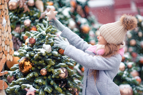 Foto Murales Little happy girl near fir-tree branch in snow for new year.