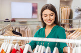 fashion, shopping and people concept - happy woman choosing clothes in clothing store