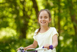 childhood, leisure and people concept - happy little girl with bicycle in summer