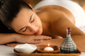 Attractive woman relaxing in spa next to candle and essential oil. © karelnoppe