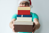 Guy wearing Santa hat and holding stacked gift boxes. Blurred man looking at camera. Gifts concept. Isolated front view on white background. - 238536411
