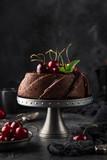 delicious chocolate bundt cake with fresh cherry on dark background