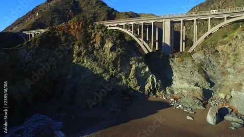 Fototapeta Aerial reveal of bridge with river flowing through it, panning towards the ocean with beautiful colors.