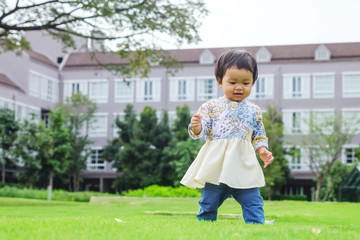 Closeup happy asian girl stand on grass floor in the garden background with fun motion