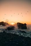 Tramonto sugli scogli con schizzi di acqua che si infrangono nelle rocce. Oceano.