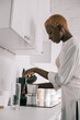 african american woman preparing beverage in coffee pot