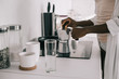 cropped view of african american woman preparing coffee in white kitchen