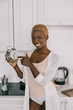 cheerful african american woman pointing at clock in white kitchen