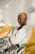 beautiful african american woman relaxing on yellow sofa
