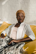 confident african american woman resting on yellow sofa