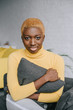 african american woman with short hair hugging grey pillow