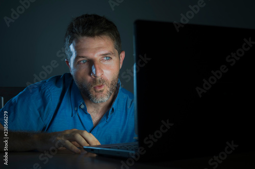 young aroused and excited sex addict man watching porn mobile online in laptop computer light night at home in pornography addiction internet pornographic content - 238566279