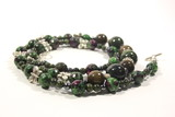 Handmade necklace of green color from multi-colored natural stones on a white background. Beautiful decoration for women.