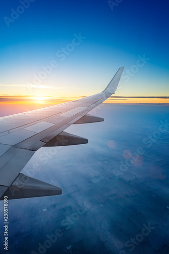 Sunset up above the clouds viewed inflight on a passenger airplane.