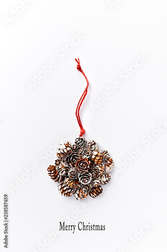 Symbolic Christmas ball made from natural cones. White background. Copy space. Flatlay