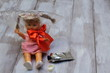 Lost childhood. Drugs and children. Doll with plastic bag, red satin bow, glue tube on light wooden background.
