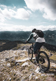 Mountain biker descending from a summit in the Alps