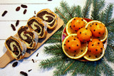 Boże Narodzenie, świąteczne przysmaki, makowiec, mandarynki i plasterki pomarańczy ozdobione goździkami, gałązki świerku
