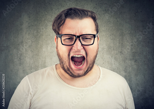 Leinwanddruck Bild Screaming chunky man in eyeglasses