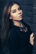 Leinwanddruck Bild - Young fashion woman in black dress standing at the brick wall