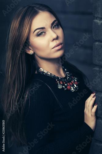 Leinwanddruck Bild Young fashion woman in black dress standing at the brick wall