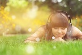 Enjoy the music,  young woman in headphones in park - 238639802