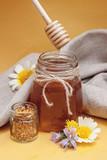 Honey jar between flowers, pollen and honey spoon in yellow background