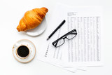 Breakfast in office with croissant and coffee on the work desk with documents and glasses on white background top view