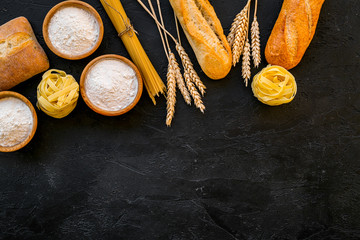Bakery production, making bread and pasta. Fresh bread and raw pasta near flour in bowl and wheat ears on black background top view space for text