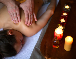 Male hands massaging female back and neck in SPA. © Stavros