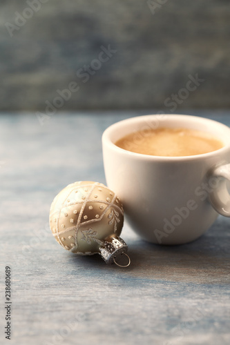 Christmas bauble and a cup of coffee . Christmas time. Rustic wooden background. Copy space.