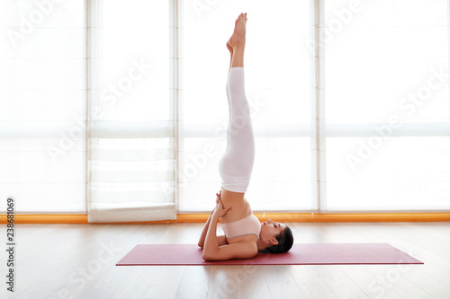 Fototapeta young woman practices yoga at  gym by window